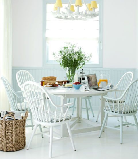 breakfast table with windsor chairs and a bird chandelier overhead