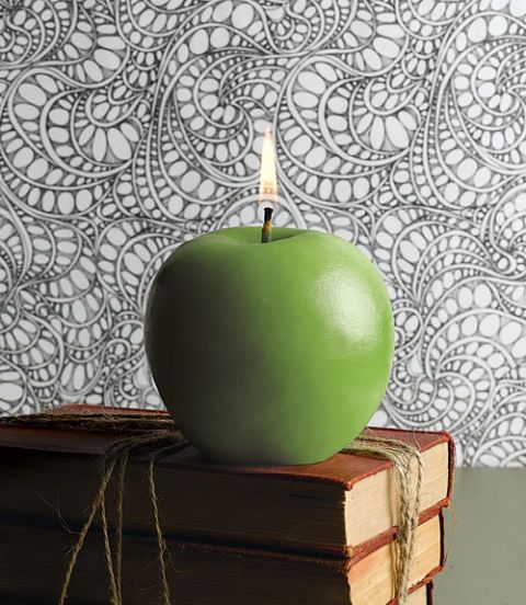 granny smith apple candle on top of books