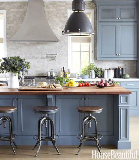 "The kitchen is a favorite place to host casual lunches and dinners. ""The mahogany-topped island can easily fit 12 stools,"" Come see 36 Best Beautiful Blue and White Kitchens to Love! #blueandwhite #bluekitchen #kitchendesign #kitchendecor #decorinspiration #beautifulkitchen"