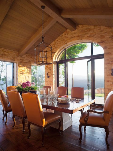 dining room in a stone and wood pavilion with large doors to the outside