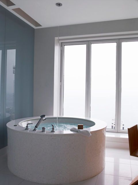 a circular jacuzzi tub in front of floor to ceiling windows