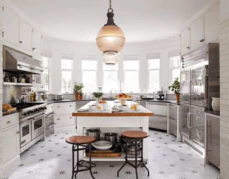 white kitchen with stainless steel appliances designed by joan schindler