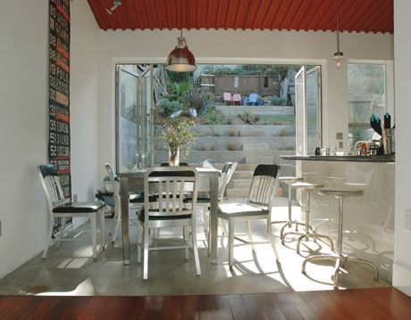 metal chairs around metal table with brick red ceiling rafters and doors opening up onto patio