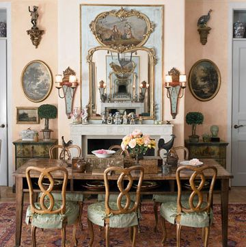 dining room area with patina colored slipcovered chairs and mirror above the mantel