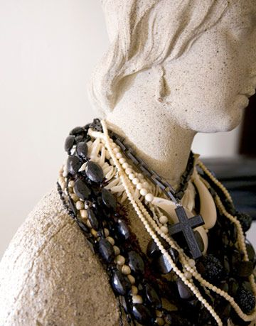stone bust of woman wearing beaded necklaces