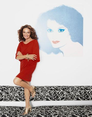 diane von furstenberg standing near a painting of herself