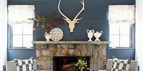 Fireplace With Matching Chairs And A Painted Floor And A White Ottoman With A Tray