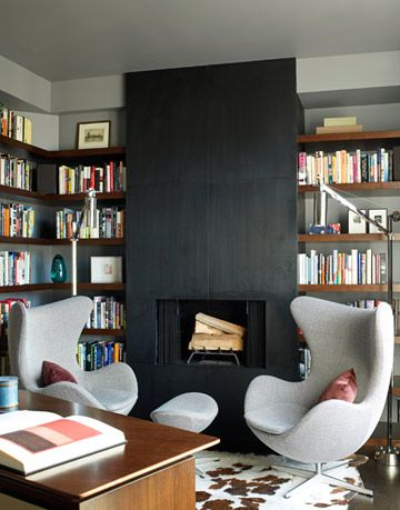 blackened steel fireplace surrounded by books and egg chairs