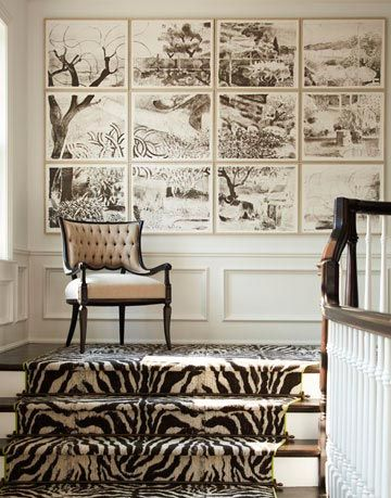 a staircase with zebra print carpeting and a mural of landscape on the wall