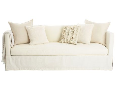 cream and white colored pillows on white sofa