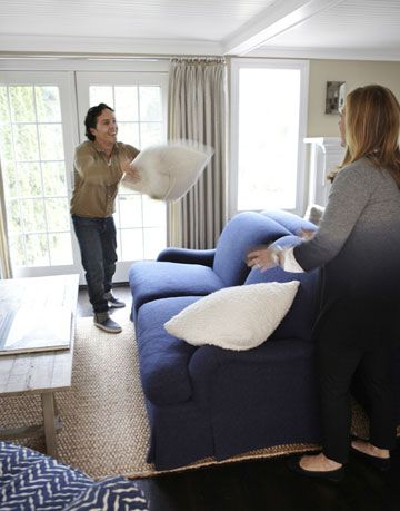man and woman throwing white pillow next to blue sofa