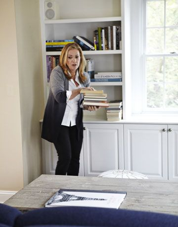 woman near a bookshelf holding books