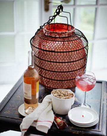 a lantern sitting on a table with a bottle of wine and some dishes