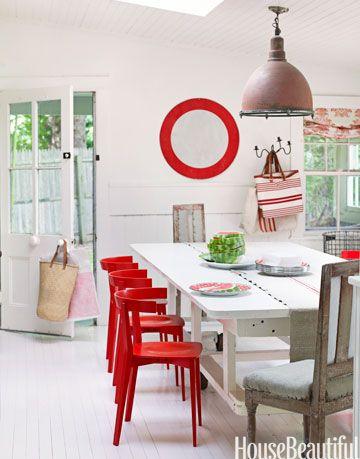 red chairs next to a white table