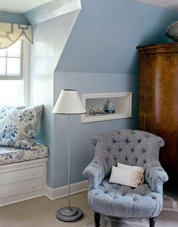 bedroom corner and window made over with blue paint an armoire a cushioned window seat a lamp and a blue armchair