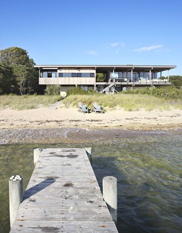 a dock on a beach in front of a modernist house