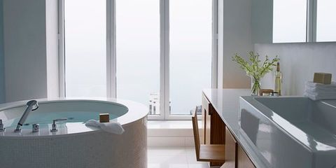 soaking tub in front of floor to ceiling windows with vanity