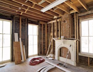 unfinished parlor with no walls but mantel framing and joists