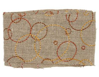 taupe fabric with orange and yellow circles embroidered on it