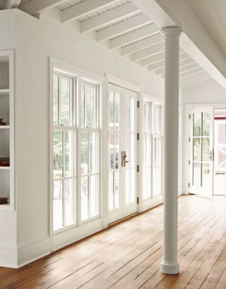 family room in restored new jersey farmhouse with wood floors and white beams and windows