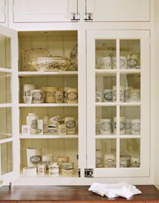 white kitchen cabinets with collection of marmalade jars