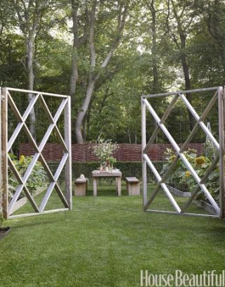 open graphic fence and gate toward wooden table in vegetable garden