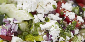 close up of chopped vegetables for salad with herbs and feta cheese
