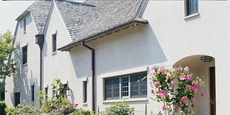 stucco house exterior with potted plants