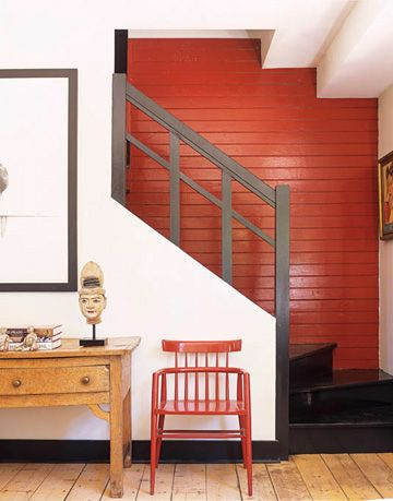 staircase with black rail and deep red wall