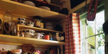 kitchen with yellow cabinets and many ceramics on the shelves