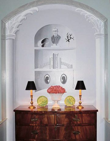 mural with console table and  trinkets in front of it