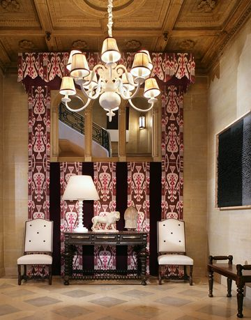 foyer with sitting area and console table and purple and pink drapes on the walls
