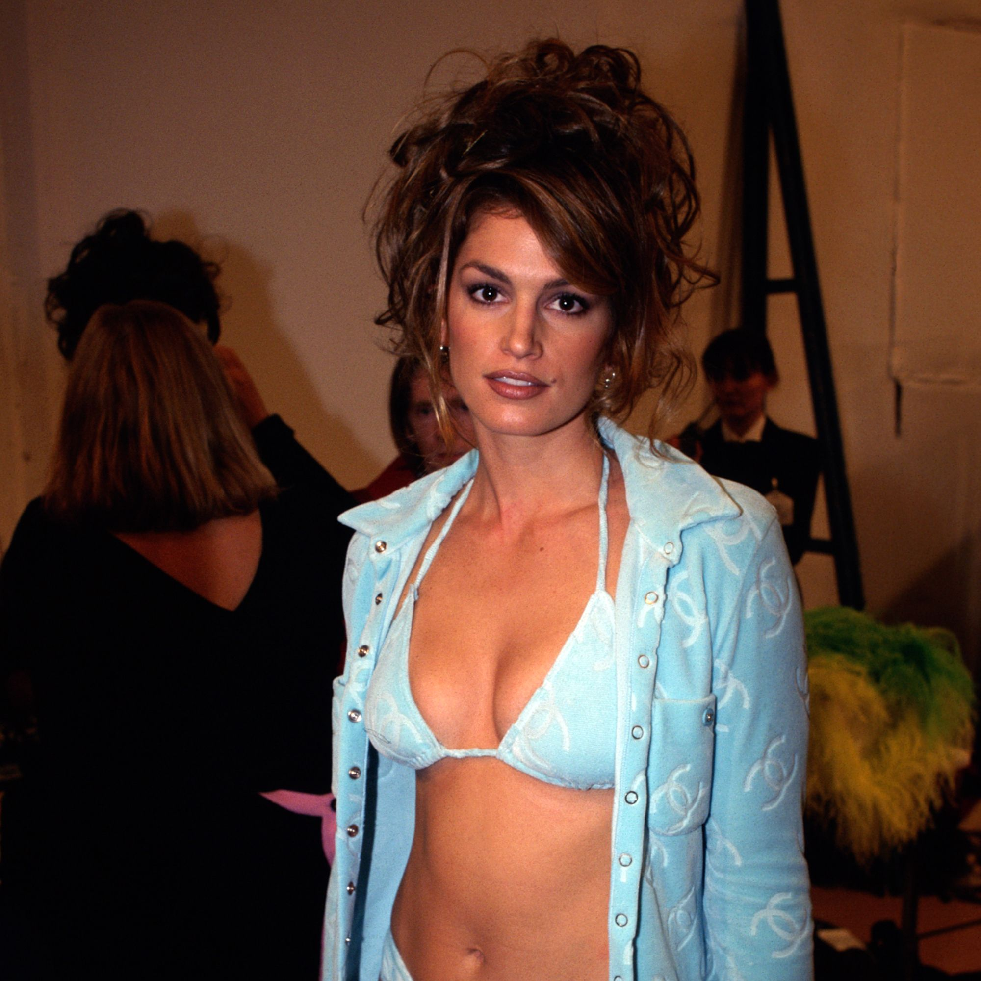 1996, France --- Supermodel Cindy Crawford wearing a powder blue bikini and shirt, backstage, at the showing of Chanel's spring-summer ready-to-wear collection. --- Image by © Photo B.D.V./CORBIS