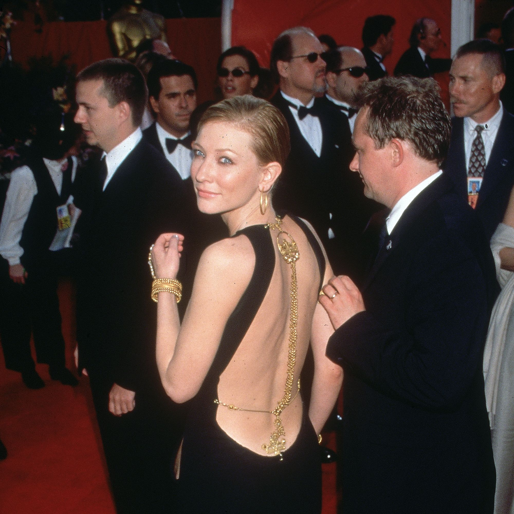 26th March 2000:  Australian actor Cate Blanchett smiles over her shoulder while walking with her husband, Andrew Upton, at the Academy Awards, Shrine Auditorium, Los Angeles, California.  Blanchett is wearing a backless black gown with decorative gold chains.  She starred in director Anthony Minghella's film, 'The Talented Mr. Ripley,' which was nominated Best Picture, and also served as a presenter at the ceremony.  (Photo by Paul Fenton/Fotos International/Getty Images)