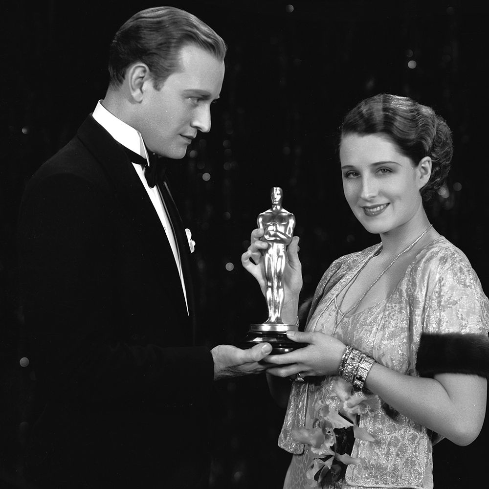 31st October 1930:  Canadian star Norma Shearer (1902 - 1983) receives a Best Actress Oscar from Conrad Nagel (1897 - 1970), for her role in 'The Divorcee'. The two co-starred as lovers in the film, which was directed by Robert Z Leonard.  (Photo via John Kobal Foundation/Getty Images)