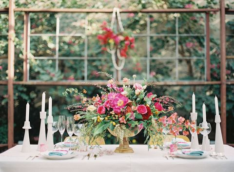"Use this classic color combo for your spring wedding: Red, pink, and gold create a vibrant visual spread, and paired with the all-white candlesticks seen in <a href=""http://michaelradfordphotography.com/blog/spring-wedding-inspiration-at-the-elysian-la"" target=""_blank"">this shoot</a>, they're a stark reminder of the beauty of new life."