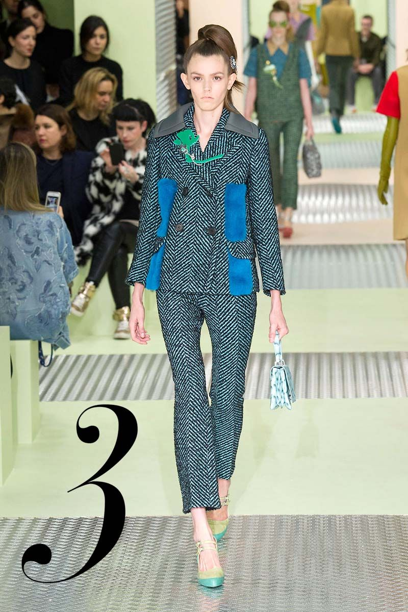 It's a mod moment for Miuccia Prada. Her perfectly proportioned '60s pantsuit has a sense of whimsy with playful touches of brightly-colored patch fur and a Perspex flower corsage.