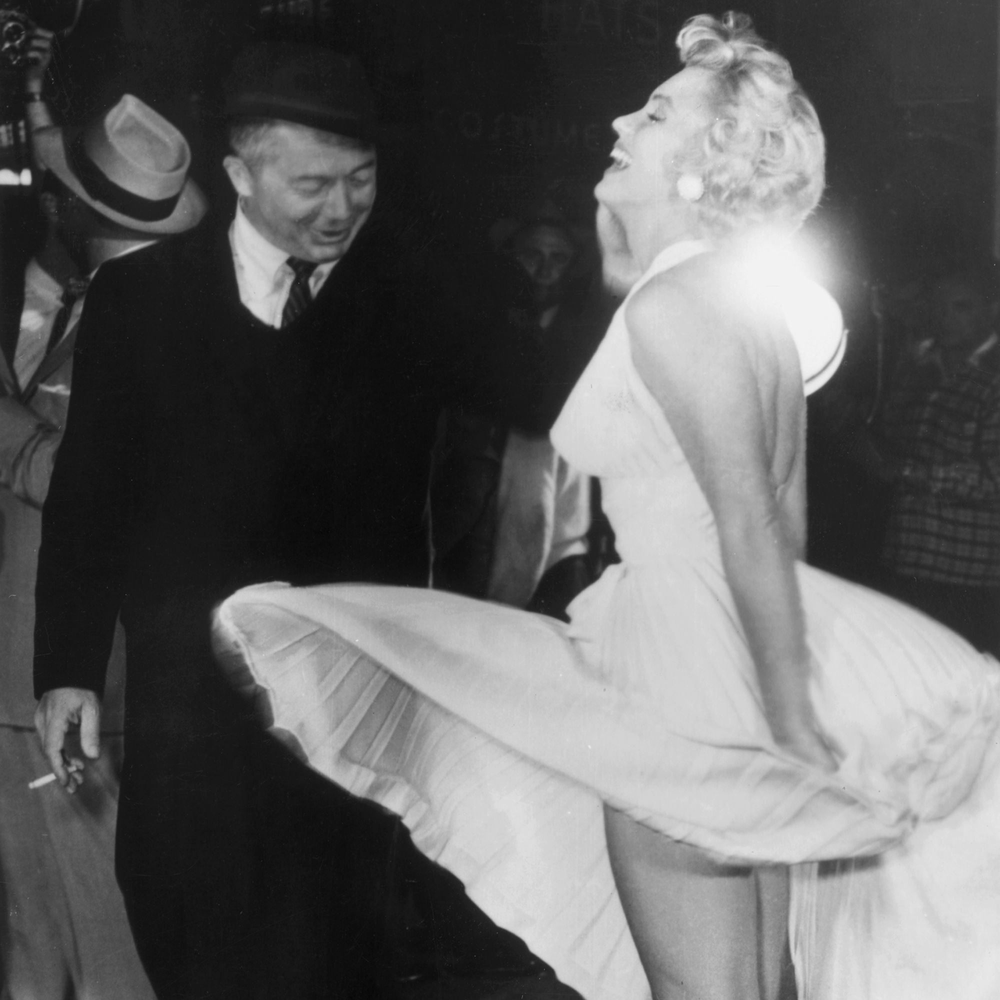 1955:  American actor Marilyn Monroe stands on a subway grate and laughs as the wind blows the skirt of her white halter dress next to Austrian-born director Billy Wilder (1906 - 2002) on the set of Wilder's film, 'The Seven Year Itch' Times Square, New York City.  (Photo by Hulton Archive/Getty Images)