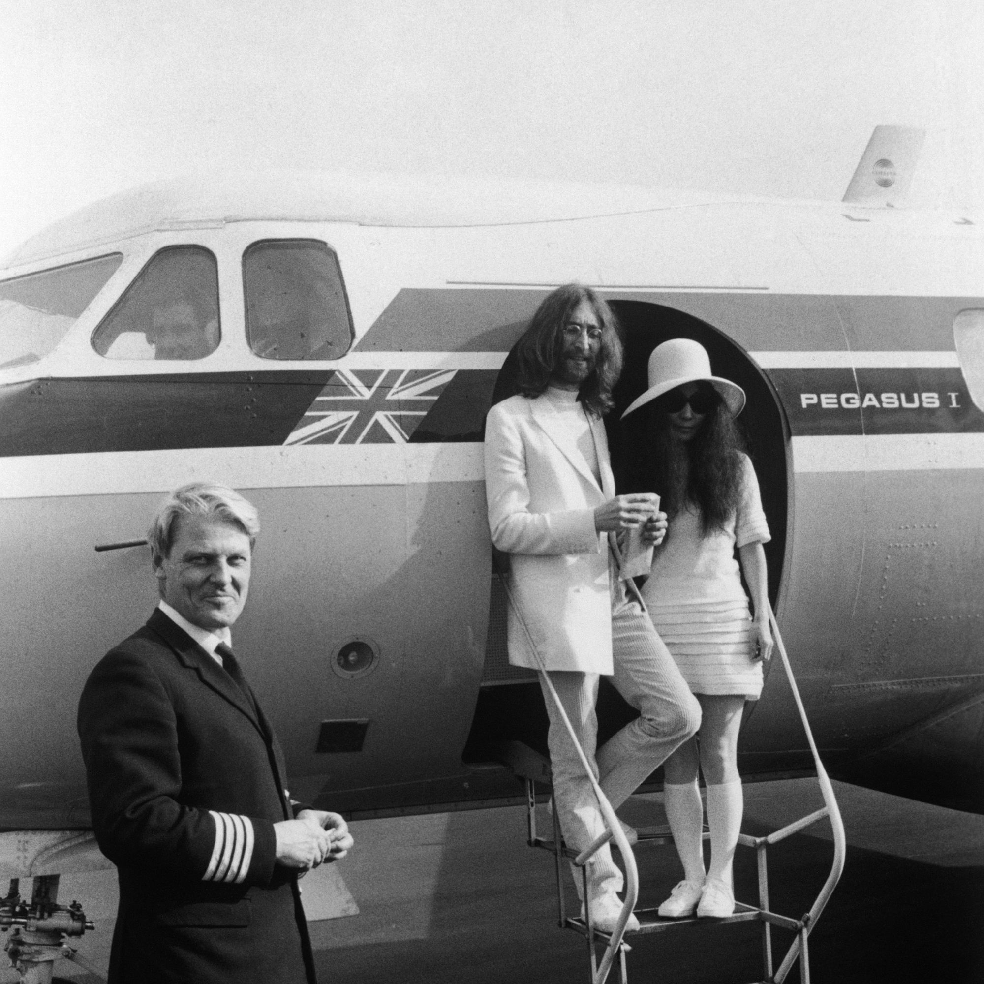 John Lennon and Yoko Ono, both dressed in white, board a private aircraft in Gibraltar after their wedding, 20th March 1969. Their pilot Trevor Copleston stands by the plane. (Photo by Simpson/Express/Getty Images)