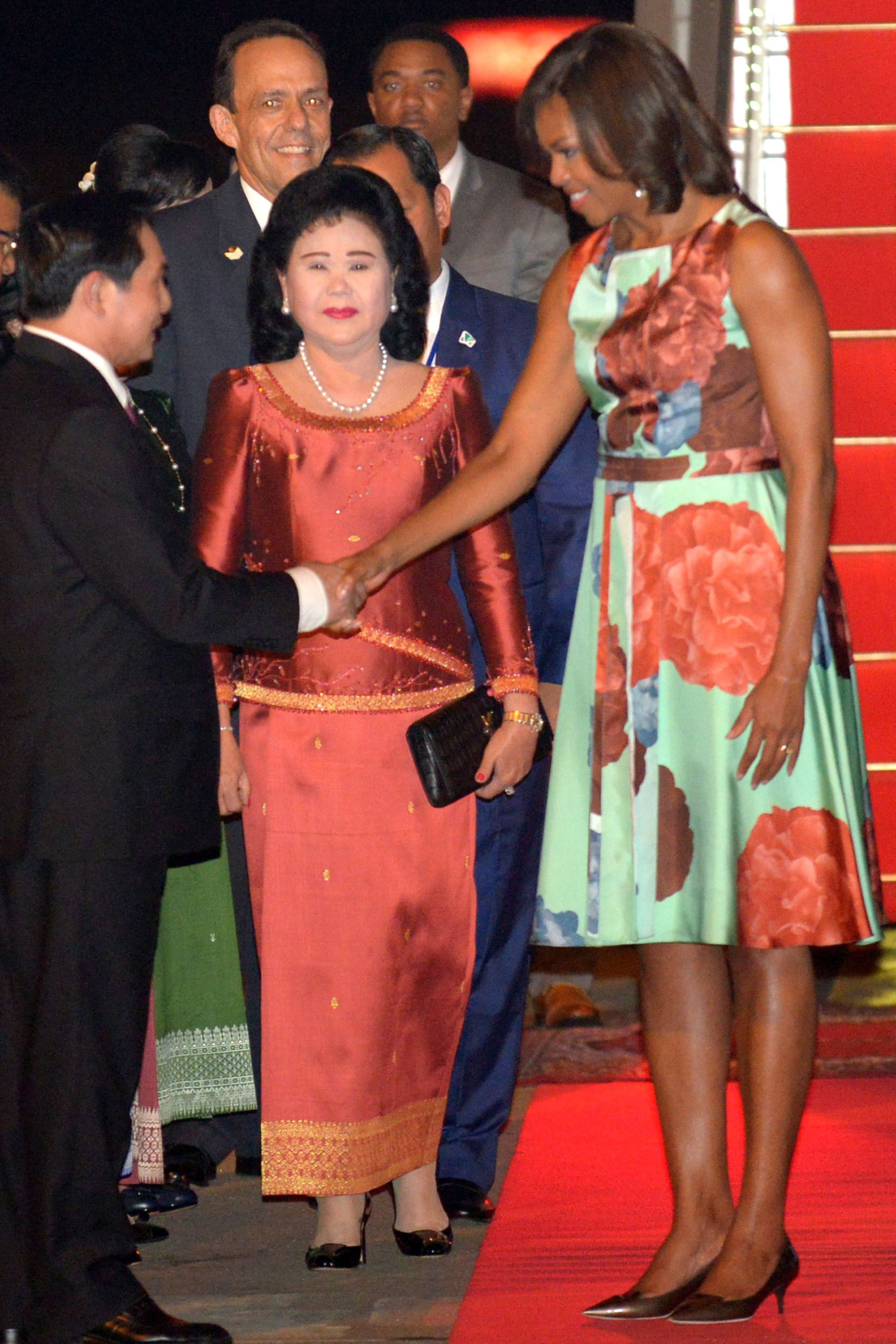 US First Lady Michelle Obama (2nd R) shakes hands with Cambodian government officials as Cambodian First Lady Bun Rany (C) welcomes her arrival at Siem Reap international airport late on March 20, 2015. Michelle Obama flew into Cambodia late March 20 becoming the first wife of a sitting US president to visit the country, part of a two-nation trip to highlight the importance of girls' education. AFP PHOTO / TANG CHHIN SOTHY        (Photo credit should read TANG CHHIN SOTHY/AFP/Getty Images)