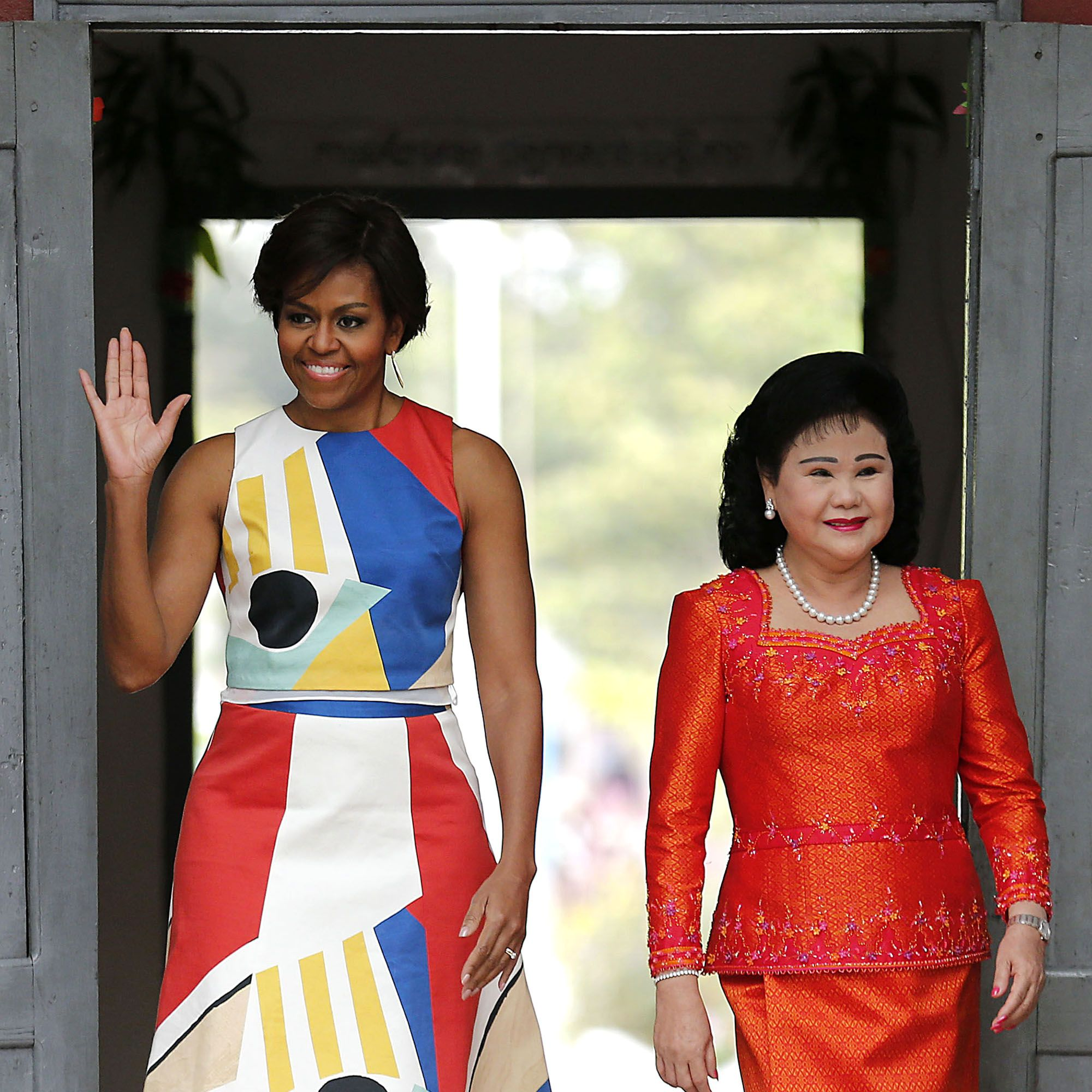 """U.S. first lady Michelle Obama, center left, and Bun Rany, the first lady of Cambodia, center right, arrive to meet with students at a local high school, Saturday, March 21, 2015, on the outskirts of Siem Reap, Cambodia. Mrs. Obama is in Cambodia to promote the education initiative """"Let Girls Learn,"""" which was launched to lift barriers that block more than 62 million girls around the world from attending school. (AP Photo/Wong Maye-E)"""
