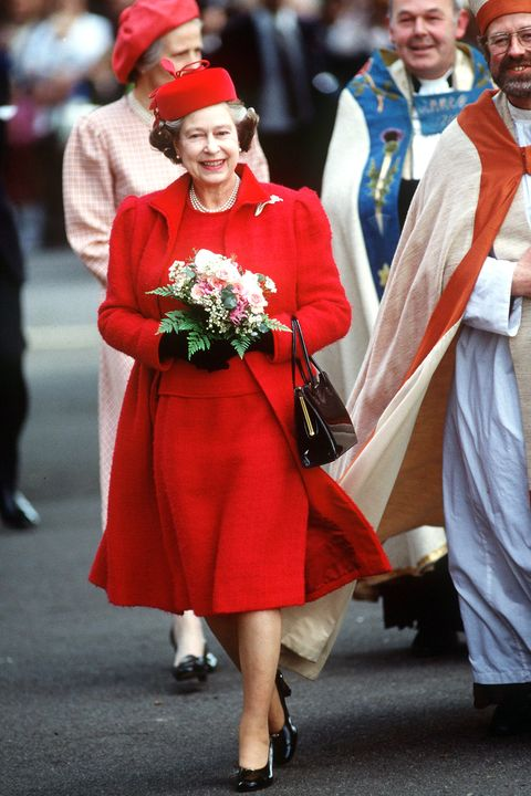 LONDON, UNITED KINGDOM - APRIL 14:  The Queen Visiting St Anne's Church In Kew. She Is Wearing A Red Coat.  (Photo by Tim Graham/Getty Images)