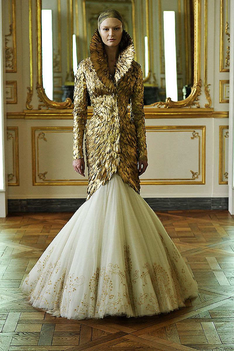 Alexander McQueen often created sculptural pieces from rare bird feathers, such as this coat, painted in gold.