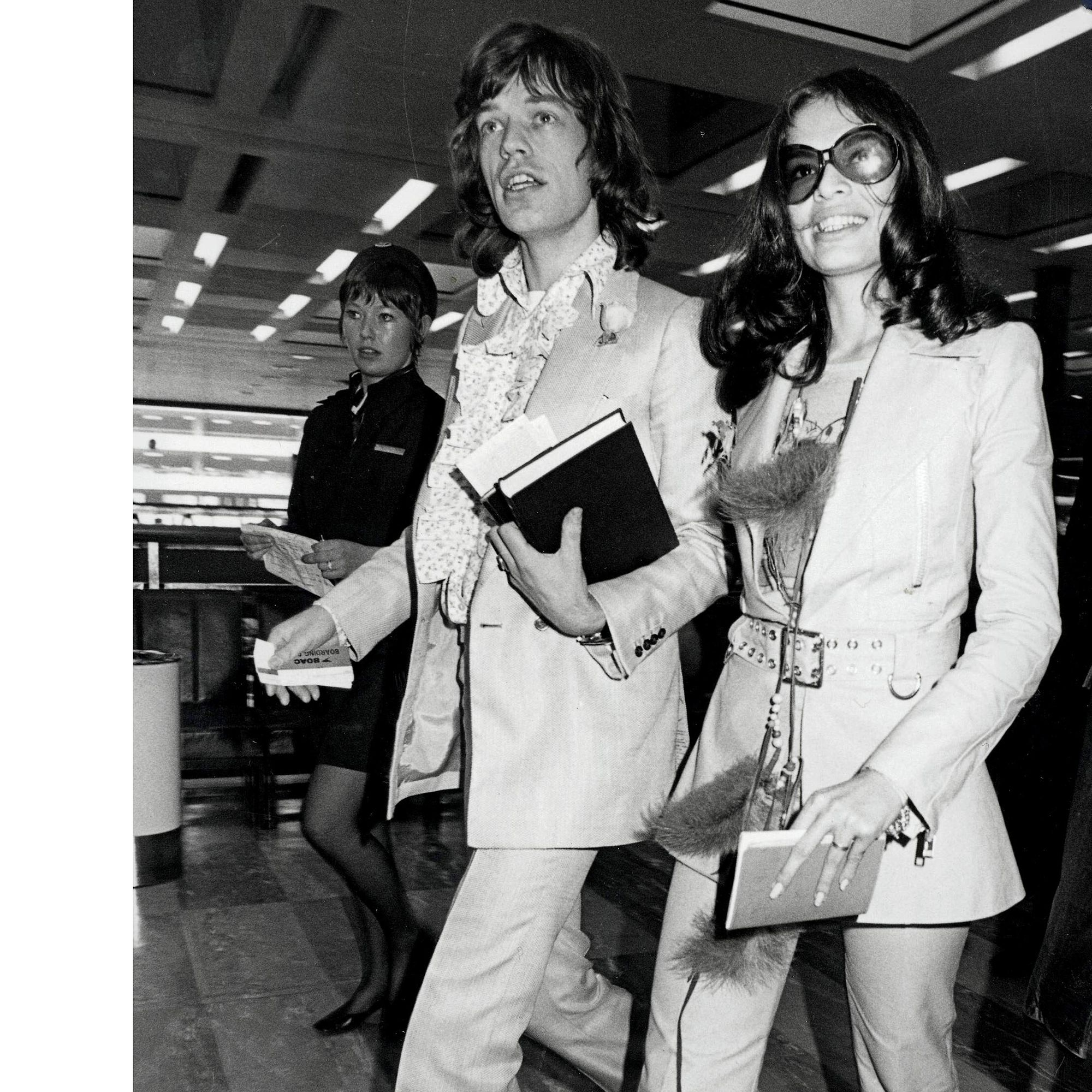 Entertainment, Music, Heathrow Airport, London, 25th November, 1970, Rolling Stones lead singer Mick jagger stands with his Nicaraguan girlfriend Bianca Perez Moreno De Macias at Heathrow Airport before flying to the Bahamas for their holiday  (Photo by Bentley Archive/Popperfoto/Getty Images)