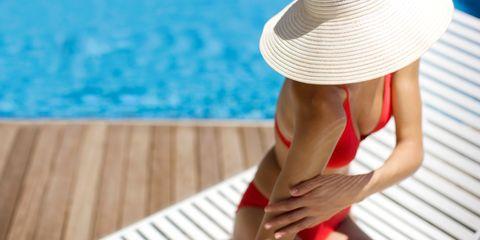 Clothing, Skin, Sun hat, Hat, Leisure, Headgear, Arm, Sun tanning, Muscle, Bikini,
