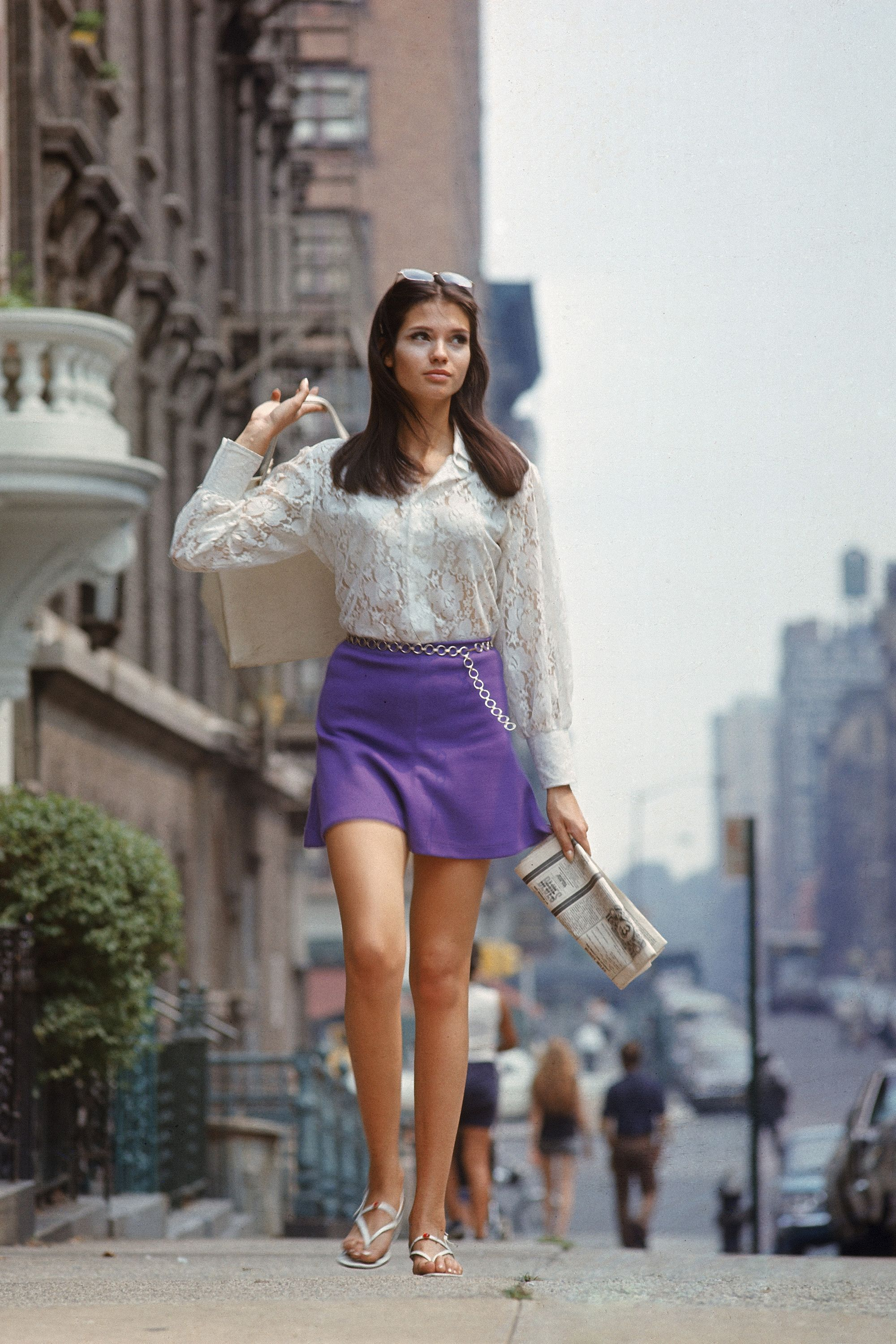 """Woman (possibly model), w. long hair wearing short skirt, lace top &amp&#x3B; sandals, walking up street, re story on """"New York look"""" in fashion."""