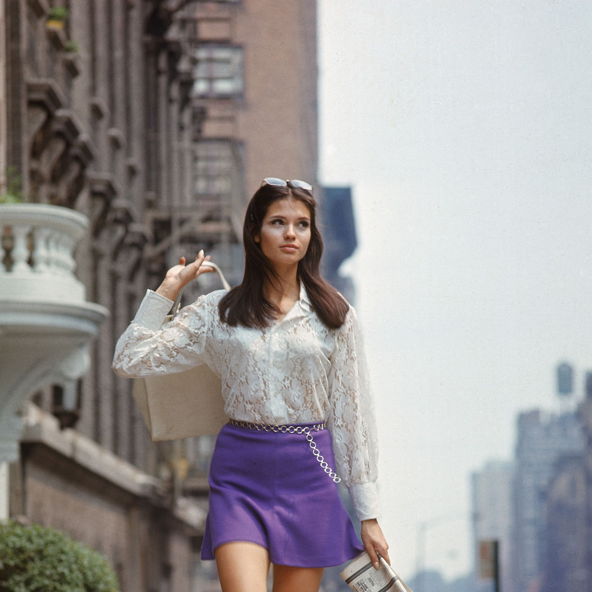 "Woman (possibly model), w. long hair wearing short skirt, lace top &amp&#x3B; sandals, walking up street, re story on ""New York look"" in fashion."