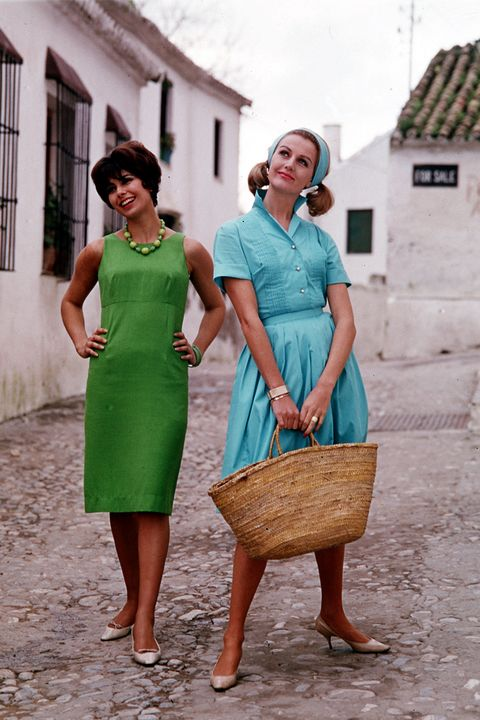 1963, Two young women wearing colourful summer dresses, one green and one light blue as they stand in a Mediterranean style street  (Photo by Popperfoto/Getty Images)