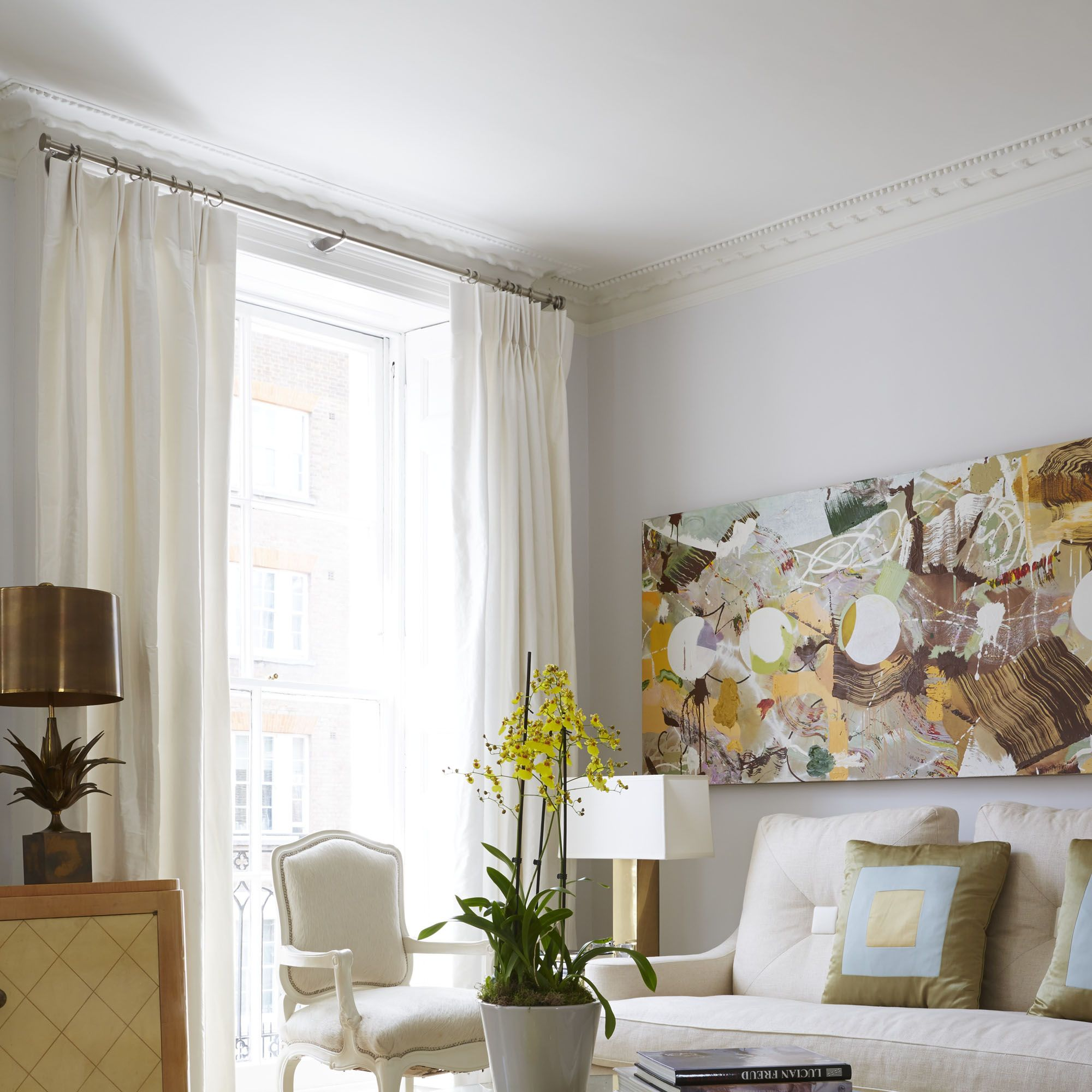 The couple's reception room showcases a 1930s Suzanne Guiguichon commode (at left), an Alain Chervet coffee table, a Fiona Rae painting, and a Jan Showers sofa.