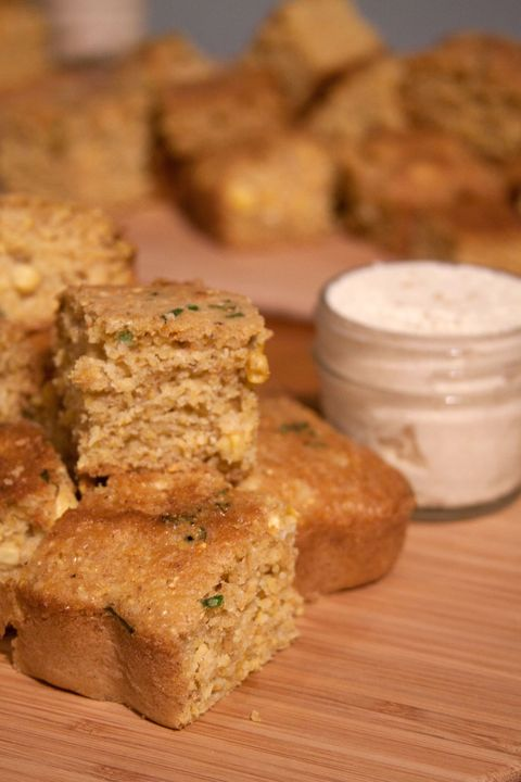 <em>Yield: 8 to 10 sqaures</em>  2 teaspoons apple cider vinegar 2 cups soy milk 1 ½ cups finely ground yellow cornmeal 1 cup all-purpose flour (or a gluten-free blend) 2 teaspoons baking soda 1 teaspoon salt ¼ cup + 2 Tbsp sugar 1 cup fresh corn kernels fresh chives, snapped into ¼ -inch pieces 1/3 cup oil (canola or coconut, melted work well)  Miso Butter  1 Tbsp sweet miso ½ cup tahini 1 stick vegan butter  Preheat your oven to 400° F.  Whisk the apple cider vinegar and soymilk together vigorously and set it aside.  In a large mixing bowl, whisk together the cornmeal, flour, baking soda, salt, and sugar.  Add the oil to the soymilk mixture and then add the wet ingredients to the dry ones, mixing until they are totally incorporated. Fold in the corn and the chives.  Pour the mixture into an 8 x 8-inch square baking dish and bake for 35 minutes, or until the top of the cornbread is firm and the edges are turning golden. Allow the bread to cool before cutting it into squares and serving.  To make the miso butter  Combine the miso and the tahini in a standing mixer with paddle attachment. Whip to combine. Add the butter, 1 Tbsp at a time, and continue to process until well combined and fluffy, adding a little water, only if necessary to reach spreadable consistency. Transfer to a small serving dish to set in the refrigerator and keep cold up to 5 days  *Cornmeal is packed with many nutrients. This whole grain is a good source of riboflavin, pantothenic acid, folate, niacin, thiamine, and vitamins B-6, E and K. Cornmeal also contains 18 amino acids and minerals such as iron, magnesium, phosphorus, potassium, zinc, copper, manganese and selenium.  © Erin O'Leary Stewart